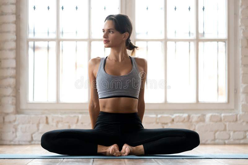 Young sporty attractive woman practicing yoga, doing Butterfly e. Xercise, baddha konasana pose, working out, wearing sportswear, pants and top, indoor full stock photos