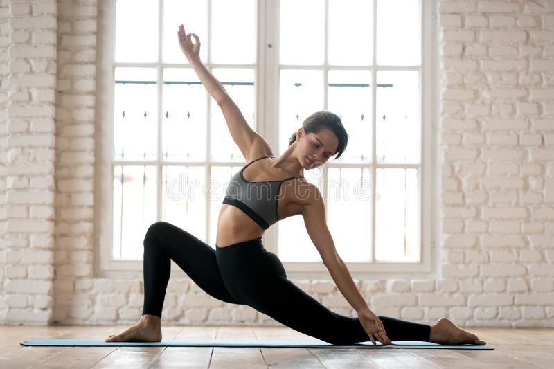 Young sporty attractive woman practicing yoga, doing Horse rider stock photo