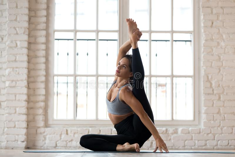 Young sporty attractive woman practicing yoga, doing Surya Yantr. Asana exercise, Compass pose, working out, wearing sportswear, black pants and top, indoor full royalty free stock photos