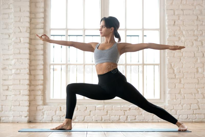 Young sporty attractive woman practicing yoga, doing Warrior Two. Exercise, Virabhadrasana 2 pose, working out, wearing sportswear, black pants and top, indoor stock photos