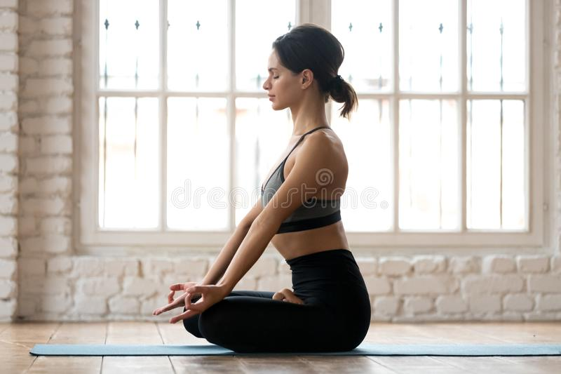 Young sporty attractive woman practicing yoga in Half Lotus pose. Young sporty attractive woman practicing yoga, doing Ardha Padmasana exercise, Half Lotus pose stock photo