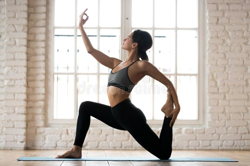 Young sporty attractive woman practicing yoga, Horse rider exerc royalty free stock photography