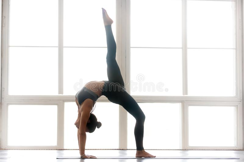 Young sporty attractive woman practicing yoga, One legged Wheel. Young sporty attractive woman practicing yoga, doing Bridge exercise, One legged Wheel pose stock photos