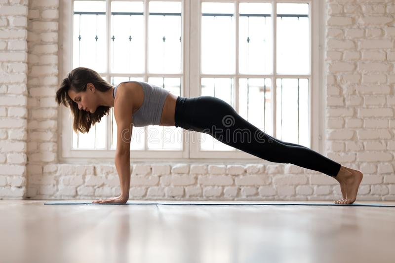 Young sporty attractive woman practicing yoga, Plank pose. Young sporty attractive woman practicing yoga, doing Push ups or press ups exercise, phalankasana stock images