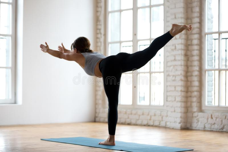 Young sporty attractive woman practicing yoga, Warrior three pos. Young sporty attractive woman practicing yoga, doing Warrior III exercise, Virabhadrasana 3 stock image