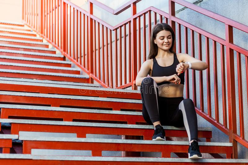 Young sporty beautiful woman having a break sitting on the red stairs after the morning jogging in the modern city, checking royalty free stock image