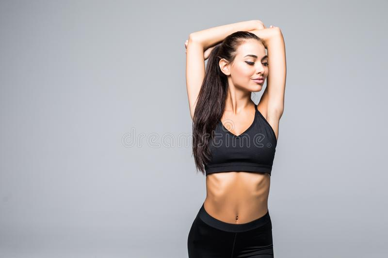 Young sporty beautiful woman stretching arms portrait isolated over white background. royalty free stock image