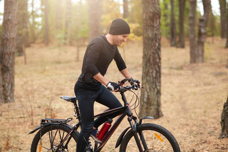 Young sporty biker riding on bike in inspirational forest landscape. Man cycling MTB on enduro trail path, covering assigned. Distance, wearing black sport wear stock photo
