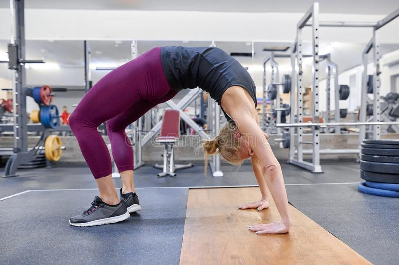 Young sporty blonde woman stretching body while doing yoga exercises at gym stock photography