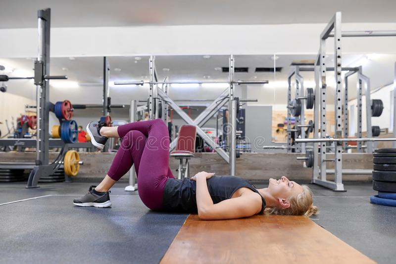 Young sporty blonde woman stretching body while doing yoga exercises at gym royalty free stock images