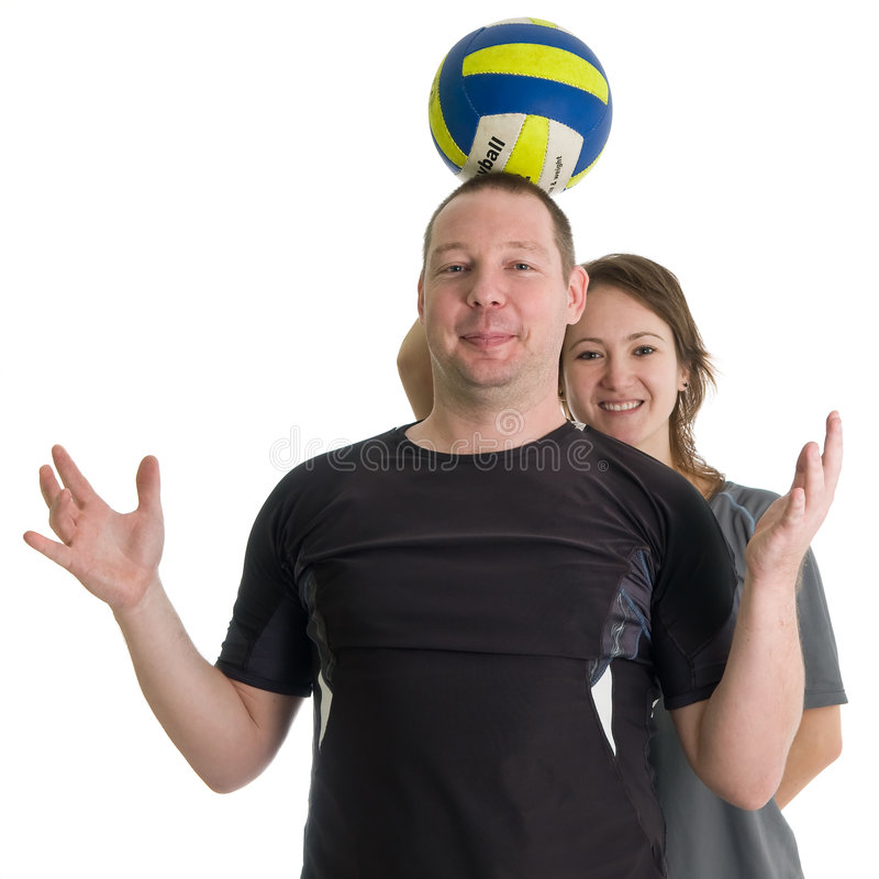 Young sporty couple. Girl is holding volleyball ball on head of her partner. Isolated over white stock photo