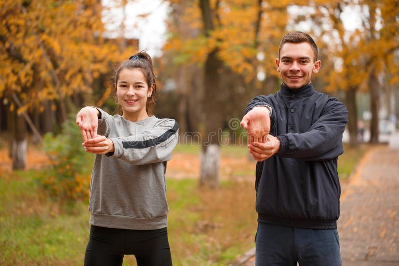 Young sporty couple doing sports in the autumn park doing an exercise on warm-up hands. royalty free stock photo