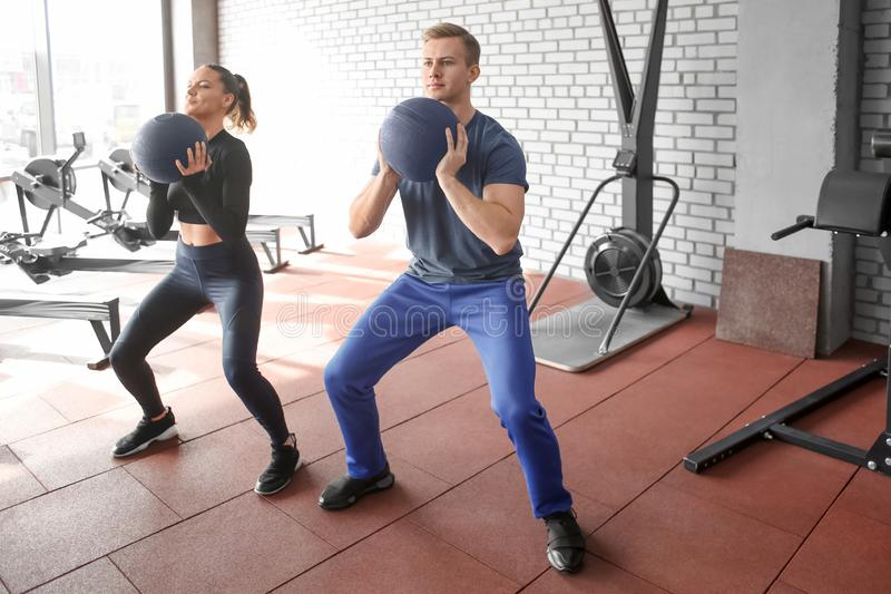 Young sporty couple working out together at gym stock photography