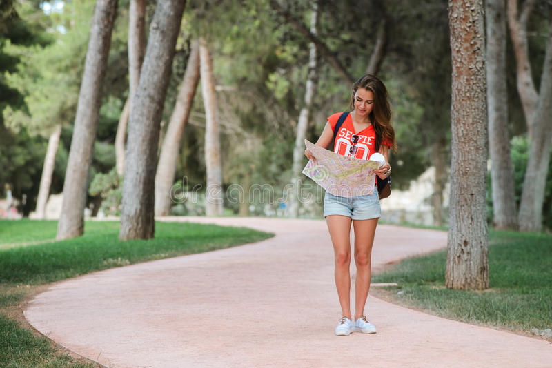 Young sporty female traveler with cute smile studying a map in park. Young sporty female traveler with cute smile studying new way on a map during amazing summer royalty free stock photos