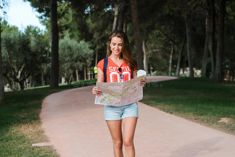 Young sporty female traveler with cute smile studying a map in park. Young sporty female traveler with cute smile studying new way on a map during amazing summer stock images