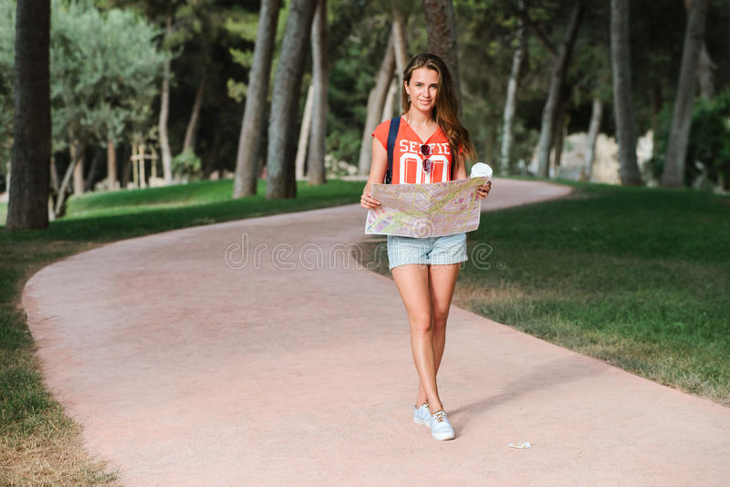 Young sporty female traveler with cute smile studying a map in park. Young sporty female traveler with cute smile studying new way on a map during amazing summer royalty free stock photography