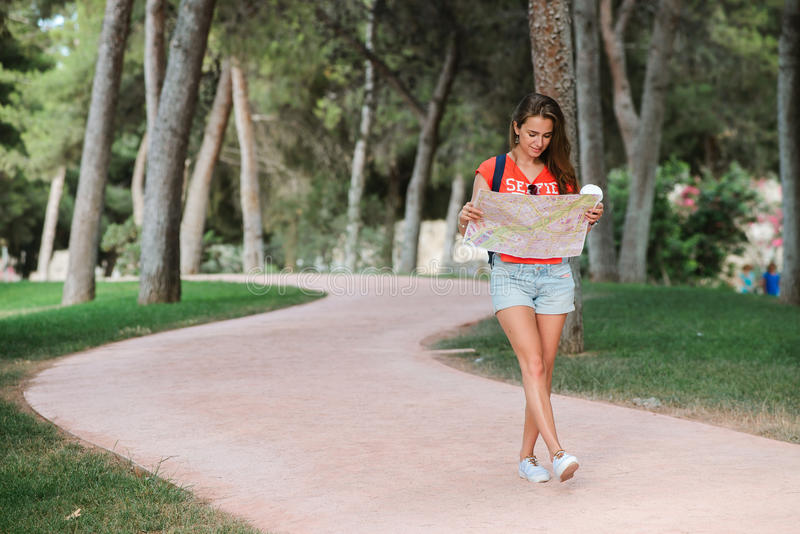 Young sporty female traveler with cute smile studying a map in park. Young sporty female traveler with cute smile studying new way on a map during amazing summer stock photography