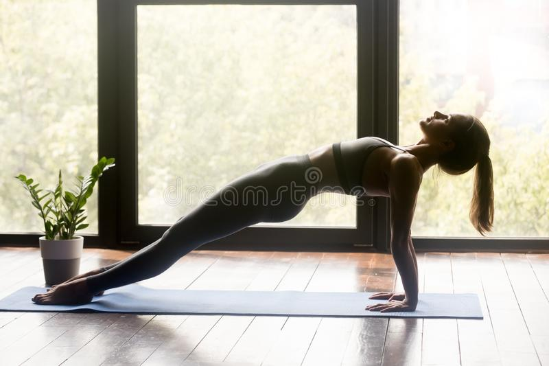 Young sporty fit woman doing Purvottanasana exercise royalty free stock photo