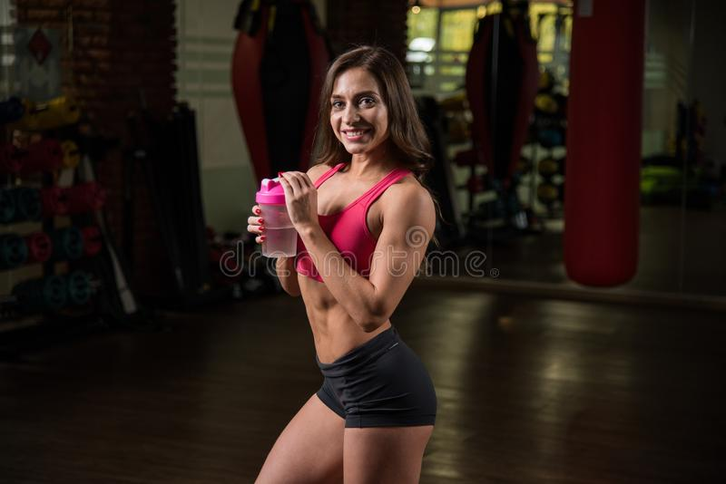 Young sporty girl in fitness hall is holding a shaker of water, fitness. royalty free stock photos