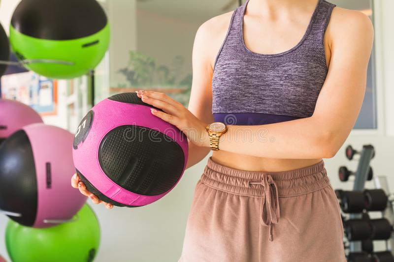 Young sporty girl holds med ball. Young sporty girl holds in her hands black pink med ball in a gym royalty free stock photo