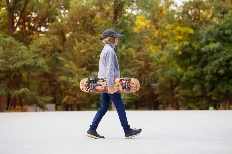 Young sporty girl riding on longboard in park royalty free stock images