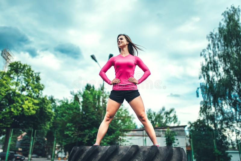 Pretty sporty girl workout outdoor with big tire royalty free stock photo