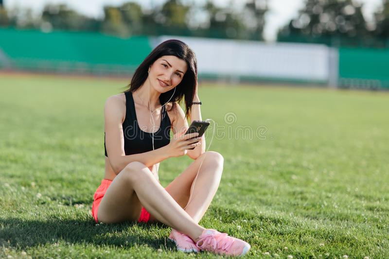 Young sporty joyful woman brunette in shorts and top sitting on the grass football field stadium and listens to music in earphones royalty free stock images