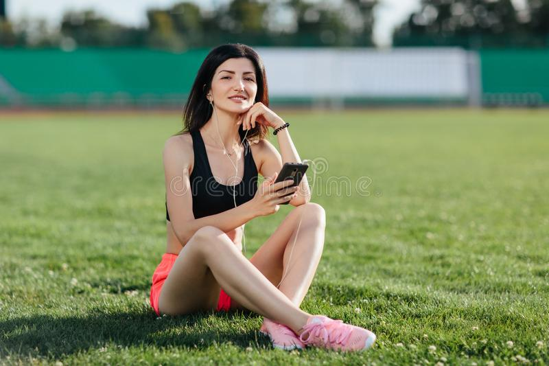 Young sporty joyful woman brunette in shorts and top sitting on the grass football field stadium and listens to music in earphones royalty free stock photography