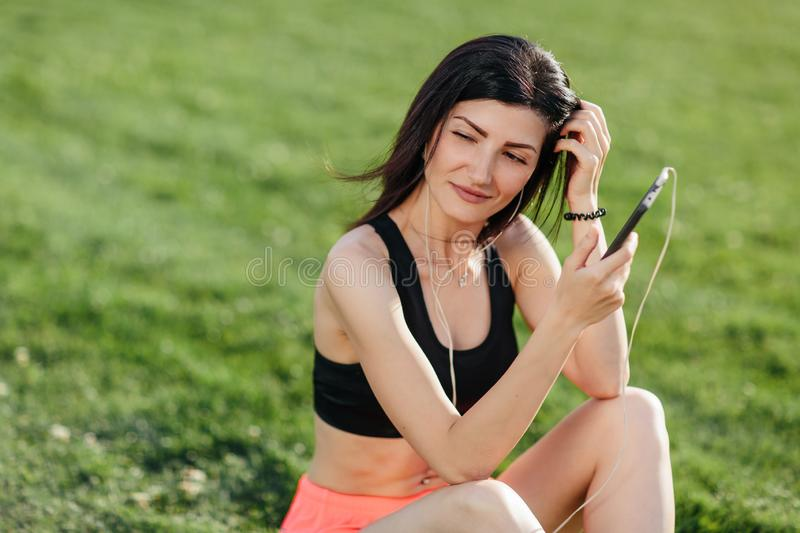 Young sporty joyful woman brunette in shorts and top sitting on the grass football field stadium and listens to music in earphones stock photo