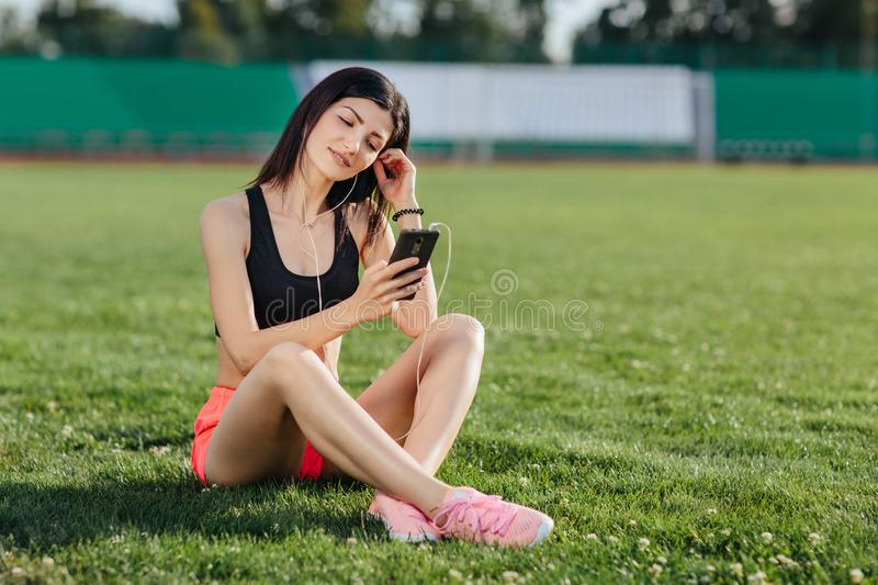 Young sporty joyful woman brunette in shorts and top sitting on the grass football field stadium and listens to music in earphones stock photos