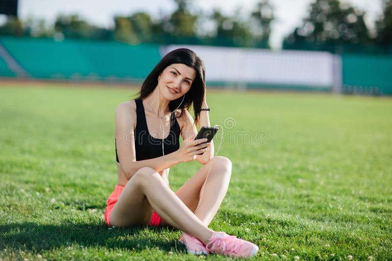 Young sporty joyful woman brunette in shorts and top sitting on the grass football field stadium and listens to music in earphones royalty free stock image
