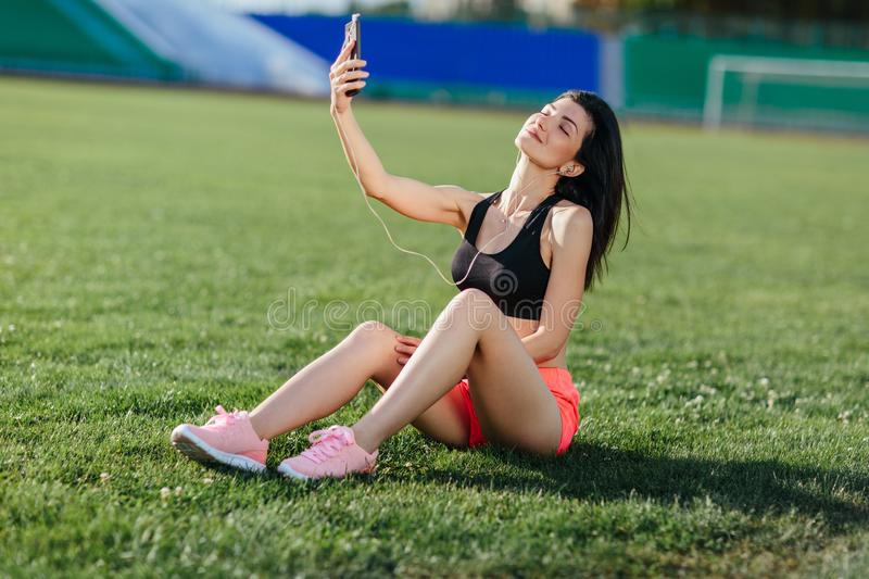 Young sporty joyful brunette woman in in shorts and top sits on the grass, listens to music in earphones and does selfie-photo on stock image