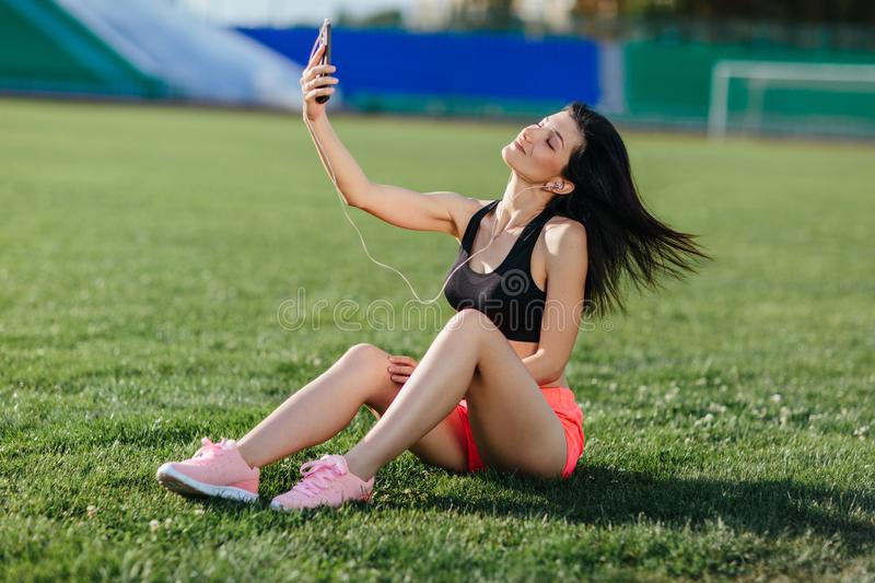 Young sporty joyful woman in sport dress sits on the grass, listens to music in earphones and does selfie-photo on the phone royalty free stock photos