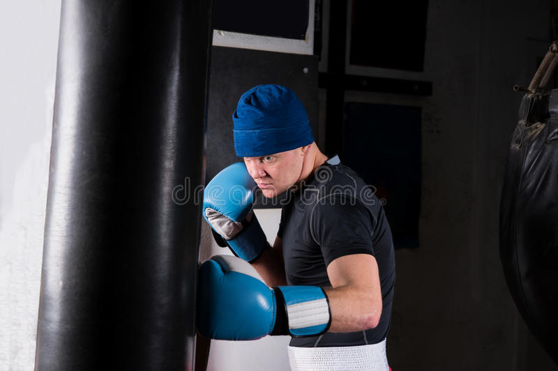 Young sporty male boxer in boxing gloves training with boxing pu stock photos
