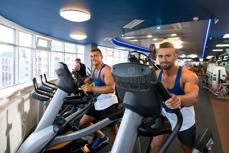 Young sporty males on simulators in a gym royalty free stock photo