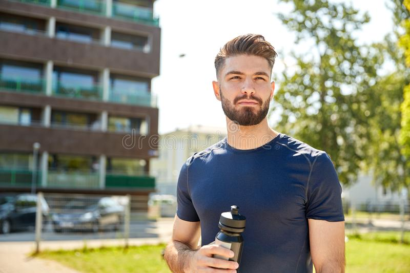 Young sporty man with bottle outdoors stock photography