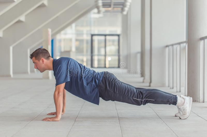Young sporty man doing push ups. Picture of a young athletic man doing push ups in a sports center, preparing for morning workout stock images