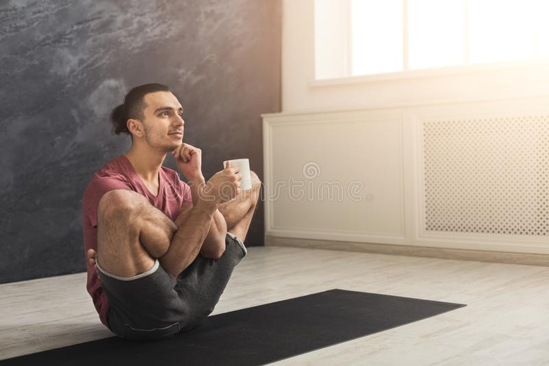 Young man in flexible yoga pose drinking tea royalty free stock photography