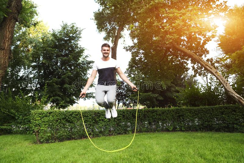 Young sporty man with jumping rope stock image