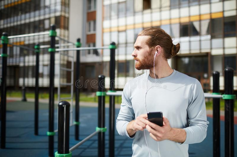 Young sporty man listening to music on sports ground stock photo