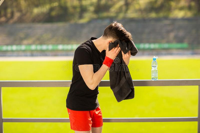 Young sporty man resting and wiping his sweat with a towel after workout sport exercises outdoors. On the background of green grass royalty free stock photography