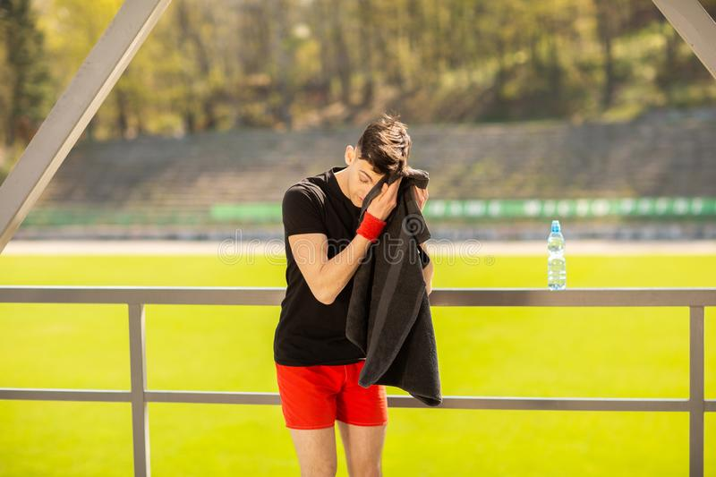 Young sporty man resting and wiping his sweat with a towel after workout sport exercises outdoors. On the background of green grass stock photo