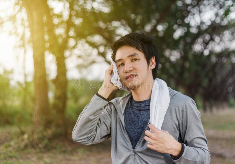 Young sporty man resting and wiping his sweat with a towel after stock photos