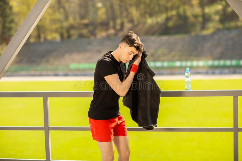 Young sporty man resting and wiping his sweat with a towel after workout sport exercises outdoors. On the background of green grass stock photography