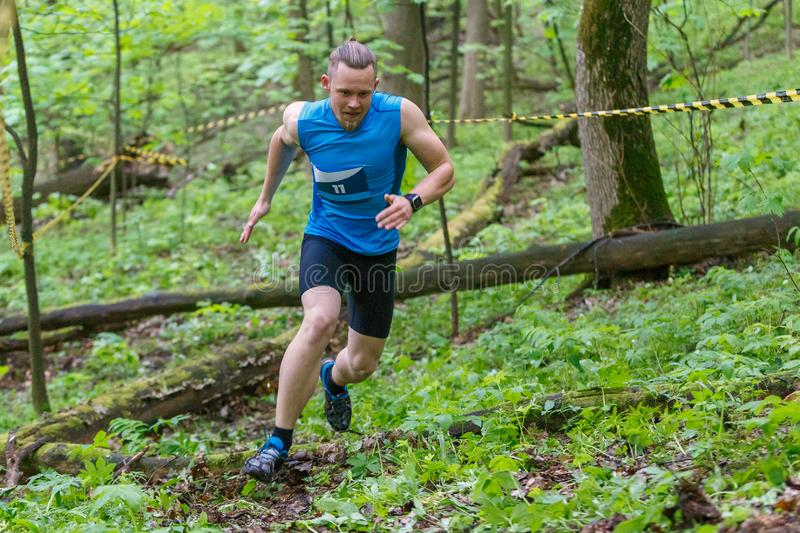 Young sporty man running trail cross in the forest stock photos