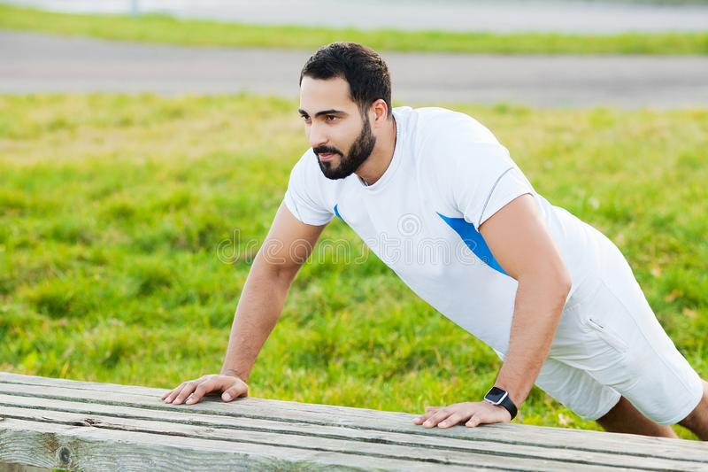Fitness in park. Young and sporty man training outdoor in sportswear. Sport, health, athletics. royalty free stock photos