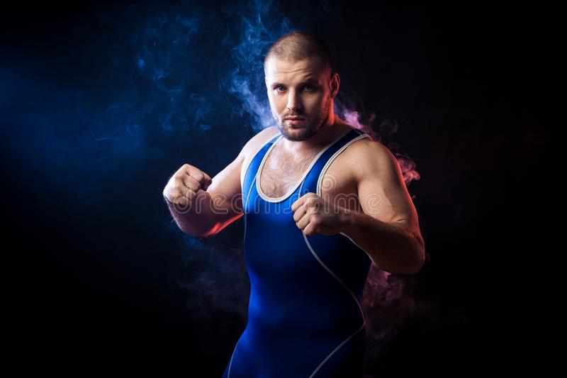 Wresler posing on black. A young sporty man wrestler in a green sports shirt and blue wrestling tights boxing against a blue and red vape smoke background on a royalty free stock image