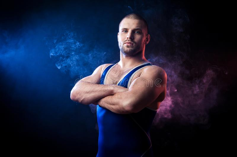 Wresler posing on black. A young sporty man wrestler in a green sports shirt and blue wrestling tights stands with arms crossed confidently against a blue and royalty free stock images