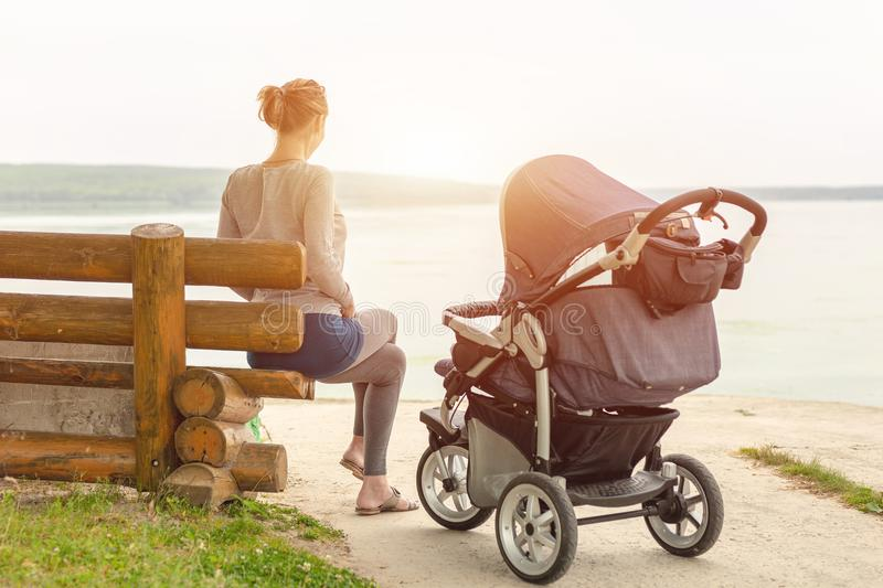 Young sporty mother with stroller sitting on wooden bench near lake or river. Mom walking with baby in pram near pond at early mor stock image