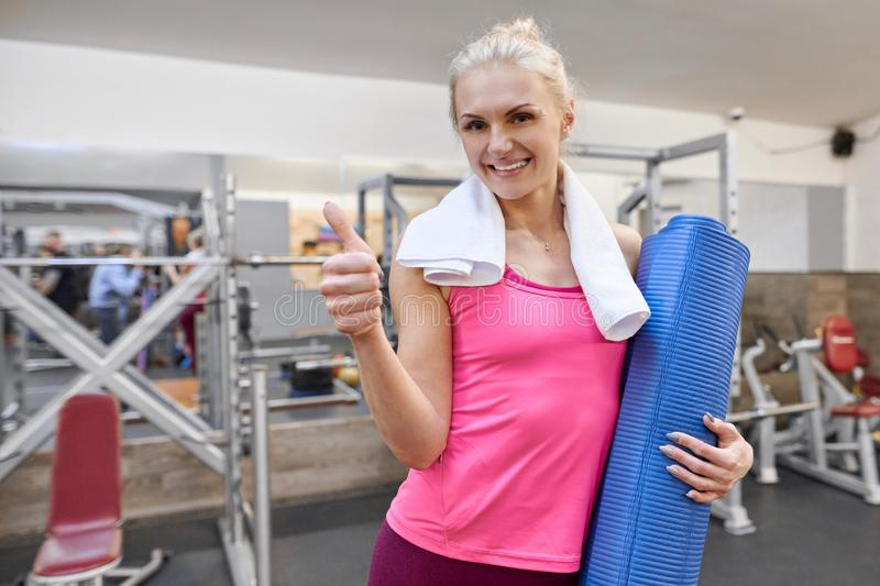 Young sporty woman blonde in gym showing thumbs up sign ok. People fitness sport healthy lifestyle concept royalty free stock photo